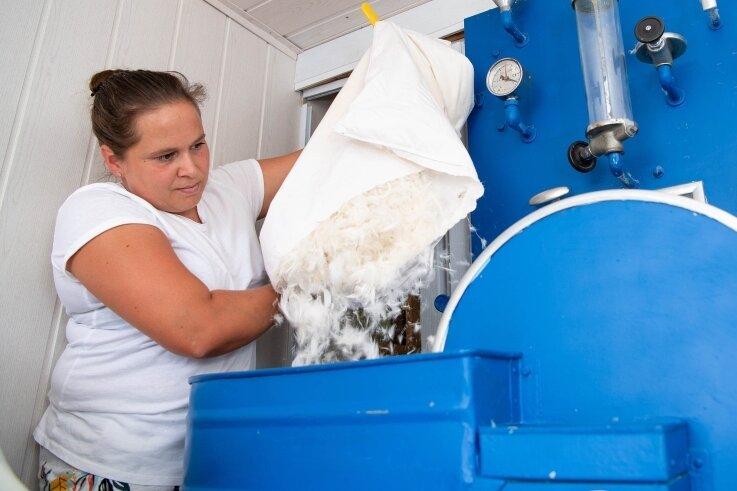 Virgina Brumbach entleert in eine Maschine die Federn eines Kopfkissens, um diese zu reinigen. Bei grobem Schmutz setzt sie heißen Dampf mit einer Temperatur von bis zu 120 Grad Celsius ein.