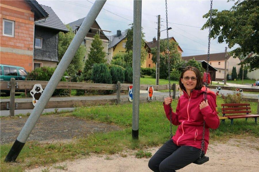 Ortsvorsteherin Kristin Winkler auf dem Kinderspielplatz. Den Zaun haben die Thierbacher Muttis selbst mit bunten Motiven verschönert.