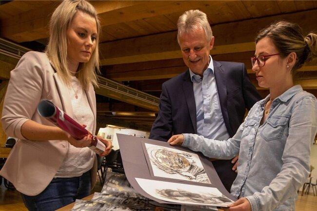 Stadtwerke-Geschäftsführer Peter Kober begutachtet mit Mitarbeiterin Mandy Wolf (links) und Malzhaus-Galeristin Julia Blei die im Nachwuchswettbewerb eingesandten Werke.