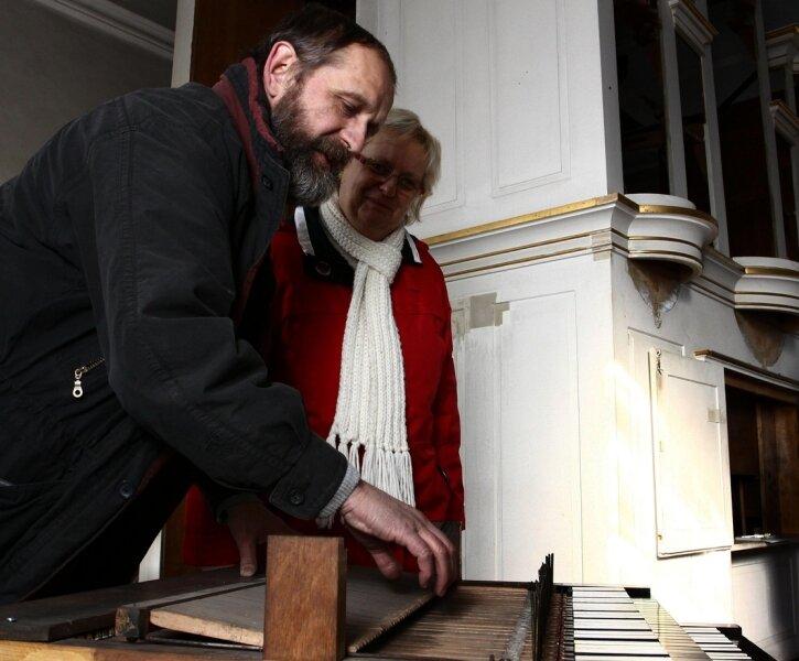 """<p class=""""artikelinhalt"""">Orgelbaumeister Christian Reinhold präsentiert Kantorin Maria Mempel die aufgearbeitete Tastatur für die Orgel. Im Hintergrund der zurzeit leere Orgelprospekt. </p>"""