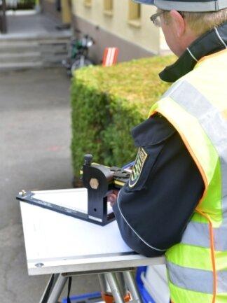Mit Hilfe eines Lasermesstisches erstellt ein Beamter vor Ort eine Unfallskizze.