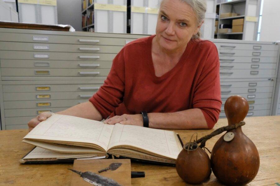 Museumsleiterin Sina Lorbeer-Klausnitz mit einem Inventarbuch des Naturkundevereins Mylau, Messerklinge und Pfeilspitze der Herero aus dem heutigen Namibia sowie Flaschenkürbis-Gefäßen aus Westafrika.