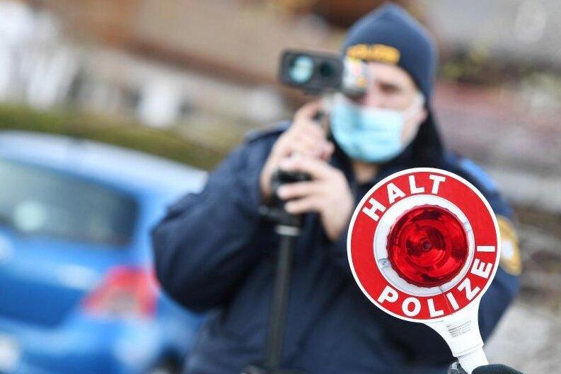 Polizisten blitzen Autofahrer. Höhere Bußgelder sollen Autofahrer dazu bringen, sich an Geschwindigkeitsbegrenzungen zu halten.