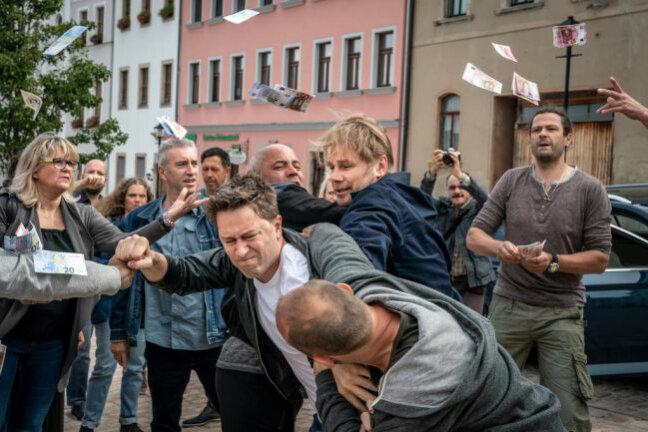 Maik in Not: Kommissar Robert Winkler (Kai Scheve, 3.v.r.) muss Maik (Adrian Topol, M.) aus einer brenzligen Situation auf dem Marktplatz von Kirchberg retten.