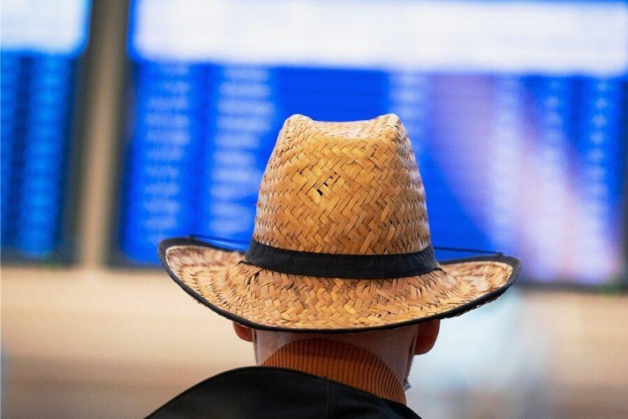 Ein Mann mit Strohhut schaut beim Warten auf eine Anzeigetafel. Nach einem erneuten Umsatzeinbruch im zu Ende gehenden Tourismusjahr rechnen Veranstalter und Reisebüros damit, frühestens 2023 in etwa das Vorkrisenniveau zu erreichen.