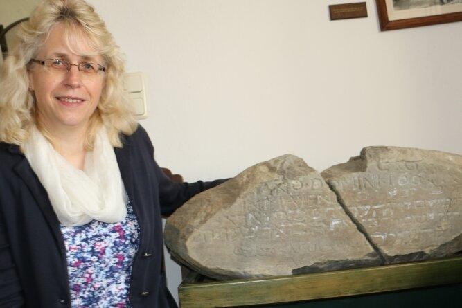 Die Reuther Pfarrerin Sabine Stepper zeigt den Stein mit dem Bibelspruch. Er stammt vom Wohnhaus des gelehrten Bauern.