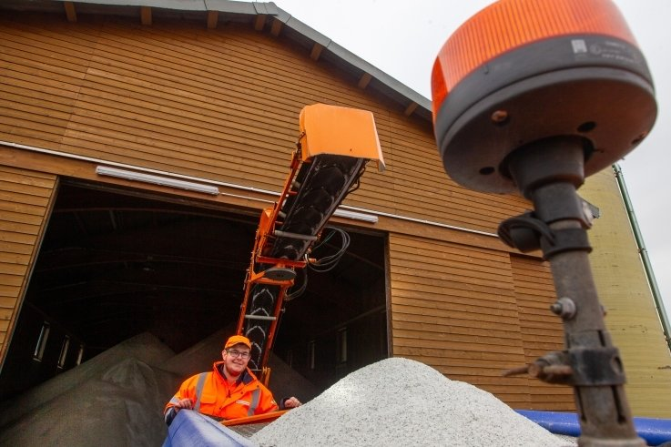 Sebastian Heinz beim Befüllen des Winterdienstfahrzeugs.