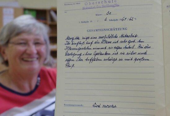 Zeitzeugin Margitta Ponikau hat den Schülern Erinnerungen an die eigene Schulzeit mitgebracht, darunter ihr Zeugnisheft.
