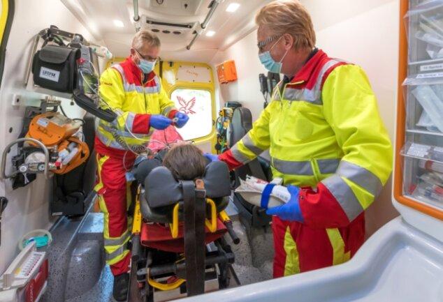 Die beiden Rettungsassistenten Volkmar Schneider und Frank Schaarschmidt (v. l.) versorgen einen Patienten vor dem Transport ins Krankenhaus im Rettungswagen.