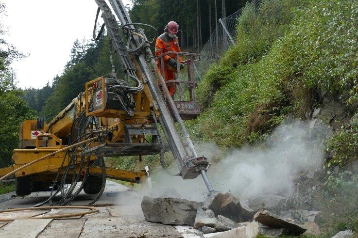 Mit einer Bohrlafette wird der mehr als zwei Tonnen schwere Felsbrocken aufgebrochen und in kleine Teile zerlegt.
