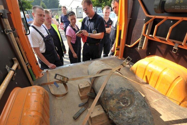 """<p class=""""artikelinhalt"""">Munitionsbergungsarbeiter Frank Hörig (vorn rechts) vom Kampfmittelbeseitigungsdienst Sachsen vor der 250-Kilogramm-Fliegerbombe, die am Mittwoch in Hirschfeld in der Erde aus Leuna gefunden wurde.</p>"""