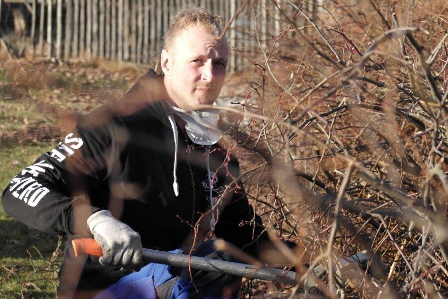 Robert Sobolewski ist mit seiner Totholzhecke fast fertig. Das Aufschichten und Verschränken der Äste ist zeitaufwendig und erfordert Übung. Mit einer Astschere entfernt er zu stark überstehende Zweige.