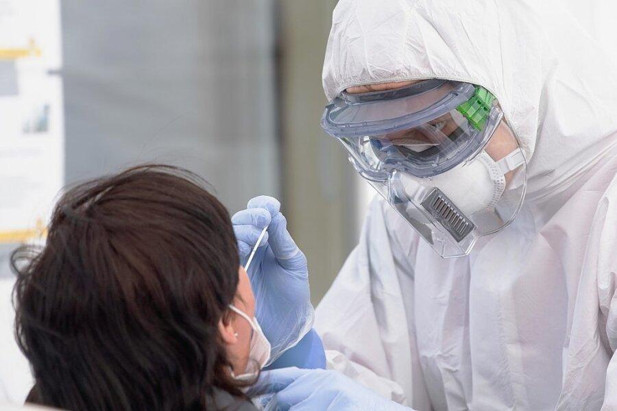 Ein Mitarbeiter des Deutschen Roten Kreuzes macht in Schutzkleidung einen Abstrich. Seit Wegfall der Testpflichten sind die Angebote gerade auf dem Land weit weniger geworden.