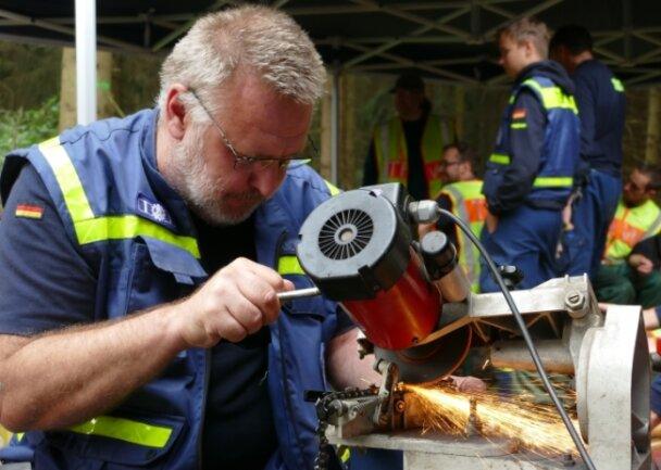 In den Mittagspausen war für die Helfer nicht nur Ausruhen angesagt. Hier schleift Ralf Mancke eine der Kettensägen nach.