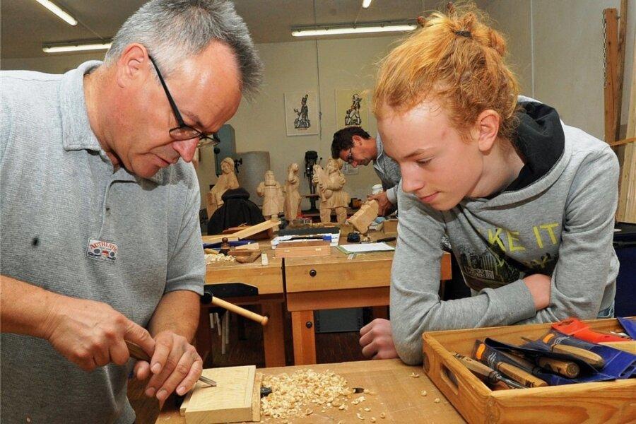 Finn Seidel besucht den Schnitzkurs in der Volkskunstschule Oederan. Kursleiter Mike Glöckner (links) gibt dem13-jährigen Flöaher Tipps, wie das Messer zu führen ist.
