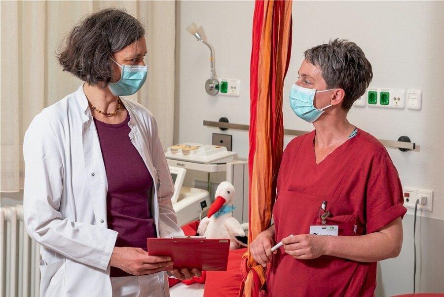 Enge Absprache zwischen Oberärztin Silke Tacke und Hebamme Susanne Keller über die Schmerzbehandlung einer Gebärenden. Als das Foto entstand, lag die Frau im Nachbarzimmer in der Gebärwanne des St. Joseph-Stifts Dresden.