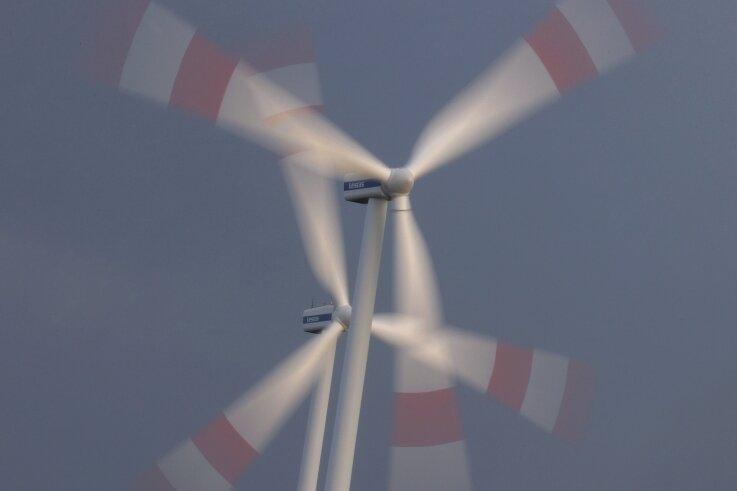Zwei Windräder drehen sich im Wind. Im Erzgebirge wird über solche Anlagen heftig diskutiert.