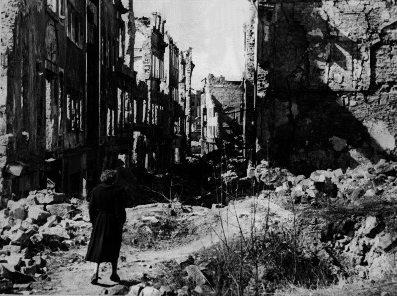 Eine Frau geht in einer Straße in Dresden an Häusern vorbei, von denen nach dem Zweiten Weltkrieg nur noch Ruinen geblieben sind. Knapp drei Monate vor Ende des Zweiten Weltkriegs legten britische und amerikanische Bomber am 13. und 14. Februar 1945 Dresden in Schutt und Asche.