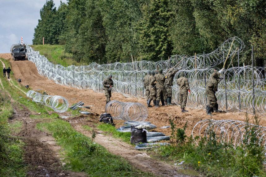 Polnische Soldaten errichten einen Stacheldrahtzaun entlang der polnisch-belarussischen Grenze.