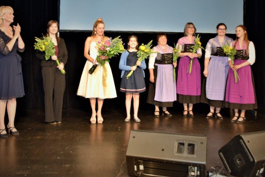 Mitwirkende an der Vogtlandsaga präsentierten sich in der Vogtlandhalle Greiz. Von links: Drehbuchautorin Sabine Maria Schoeneich, Melanie Riedel (Dorothea), Stefanie Hertel (Ella) sowie die musikalischen Mitstreiter Emily Alnajjar und die Grünbacher Folkloristen.
