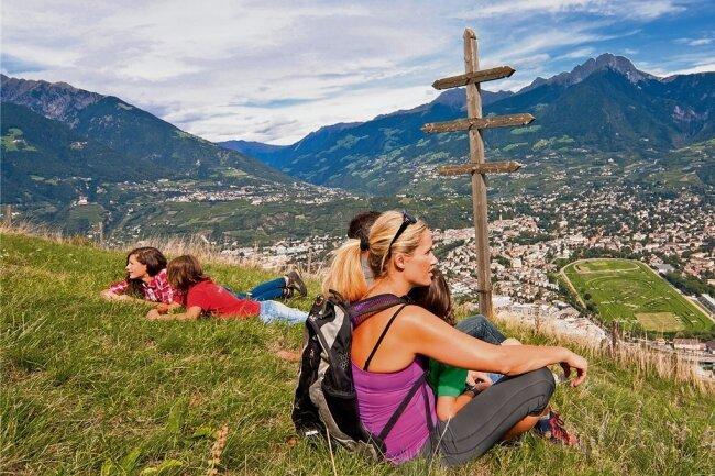 Das Wetterkreuz am Höhenweg soll das darunterliegende Marling (nicht sichtbar) vor Gewitter schützen. Von hier geht der Blick nach Dorf Tirol (l.) und zu den Gipfeln von Hirzer und Ifinger, zum Ski- und Wandergebiet Meran 2000 und nach Meran mit der Pferderennbahn.