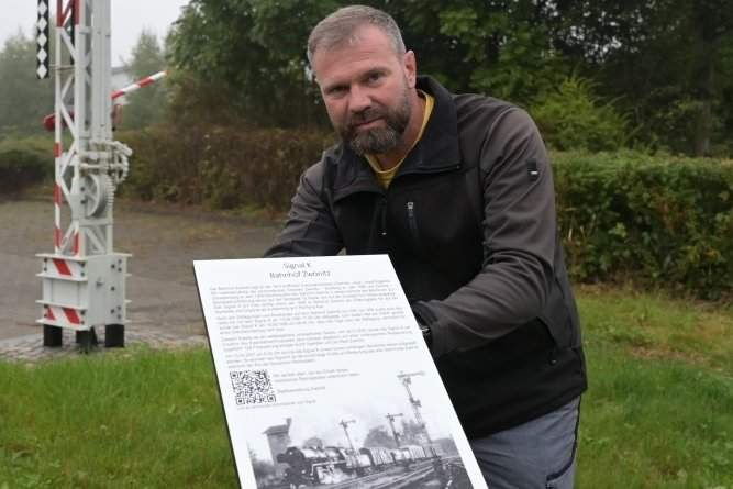 Letzte Handgriffe: Tom Schneider, Leiter des städtischen Bauhofes, überprüft die Festigkeit der neuen Info-Tafel am Bahnsignal.